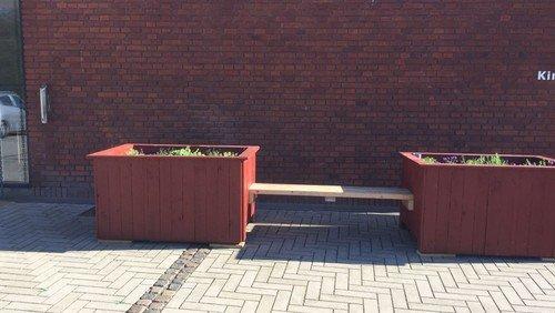 Plante-kasse-bænk foran kirken