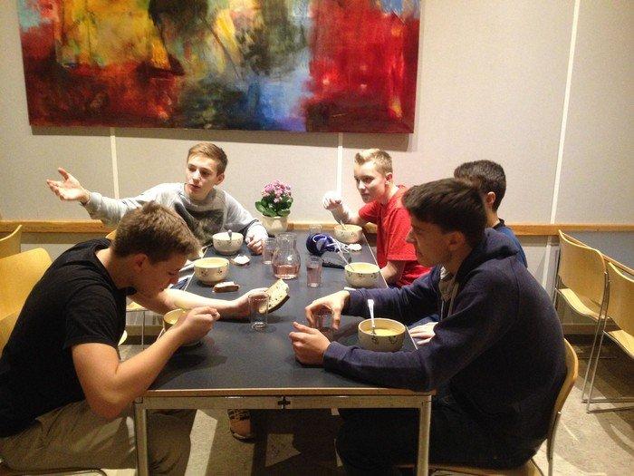 Konfirmander spiser og hygger sig ved bord foran farvestrålende maleri