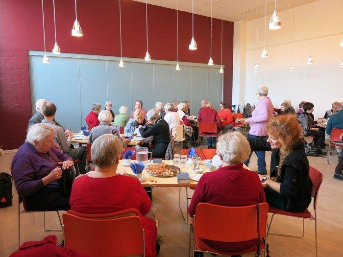 Salen fyldt med ældre mennesker som får kaffe og kage