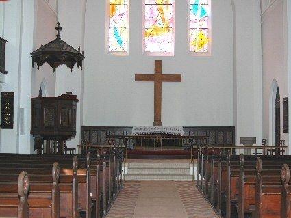 Glasmosaik i kirkens korvinduer er tegnet af Jens Urup