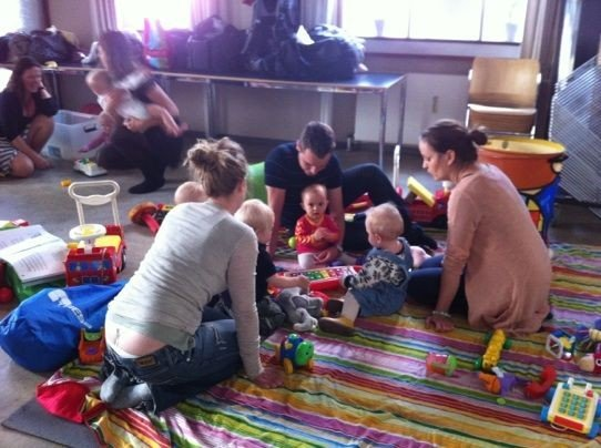 Forældre leger på spraglet tæppe med deres børn