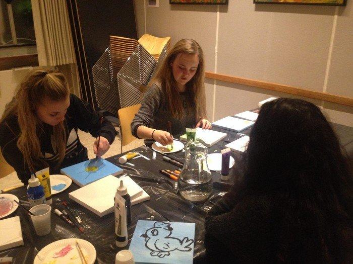 Konfirmander maler i Konfirmand-Caféen. De sidder ved et bord med lærreder, pensler og maling foran sig.