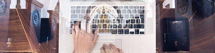 Bærbar computer foran billede af Nørre Tranders Kirke indendørs