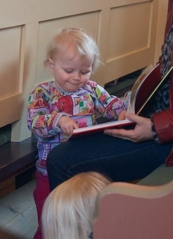 Barn kigger i bog under gudstjenesten