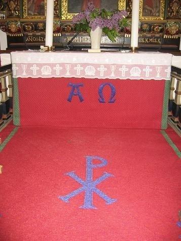 Alterpartiets vævninger med de græske symboler for Kristus.