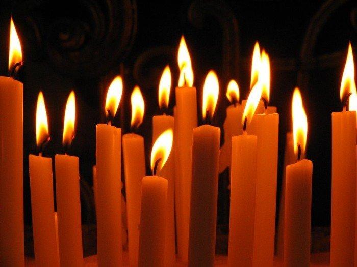 Taizeandacht - viele schmale Kerzen in Dunkelheit