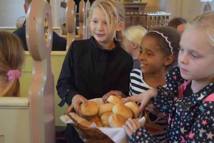 Børn deler brød ud til gudstjenesten