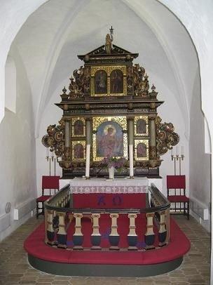 Tune kirkes kor. De røde vævninger (antependium, gulvtæppe m.m.) blev monteret 1995.