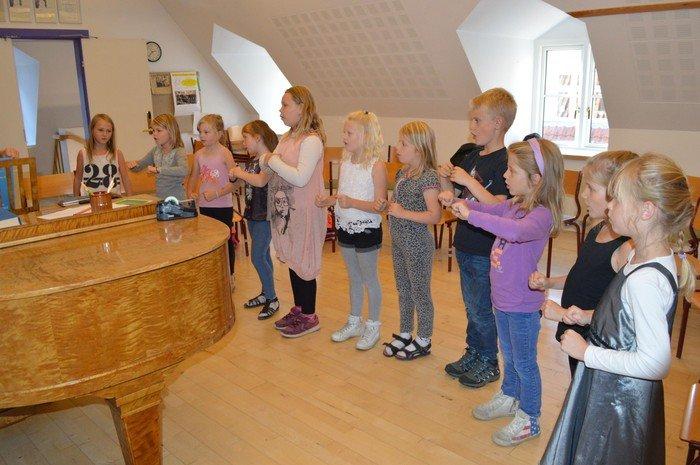 Billede af koret der øver omkring klaver