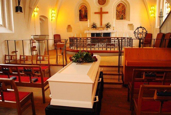 En kiste står klar til bisættelsen/begravelsen i kirken
