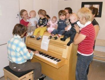 Børn og voksne omkring klaveret