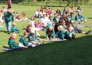 Spejdere siddende på græsset
