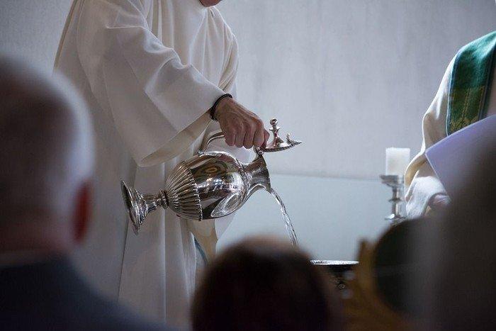 Præst hælder dåbsvand i døbefonten