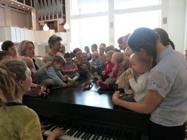 Rytmikpædagog spiller på flygel fyldt med babyer