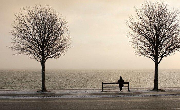 Mand sidder alene på bænk - sjælesorg