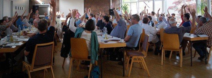 Menschen sitzen an einem langen Tisch und halten Stimmkarten in ihren erhobenen Händen.