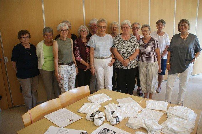 Billede af 13 kvinder, der er med i strikkecafén. Foran ligger dåbsklude på et bord.