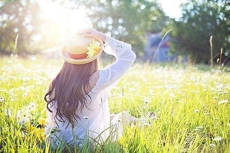 Ryggen af pige som kigger mod solen. Holder sin hat på hovedet.