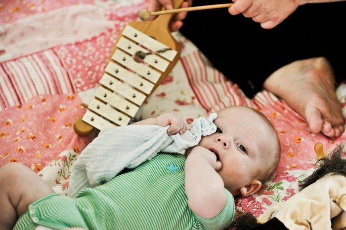Baby ligger på tæppe og lytter til xylofonspil. Modelfoto Folkekirkens Materialedatabase