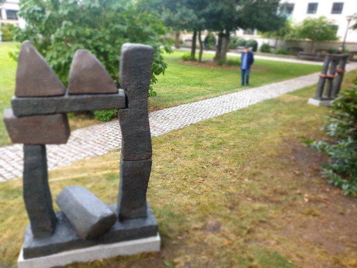 Foto af skulpturerne og en gæst i kirkehaven