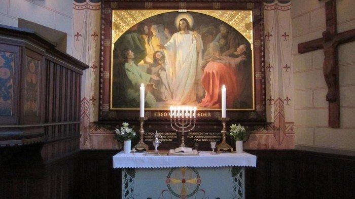 Alteret med altertavlen i Sct. Lukas. Til højre Kristus på et trækors. Til venstre prædikestolen. Alterlysene er tændte