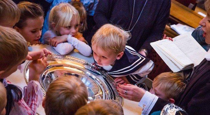 Børn samlet rundt om dåbsfad
