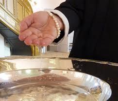 Dåbsfad og en hånd der øser vand