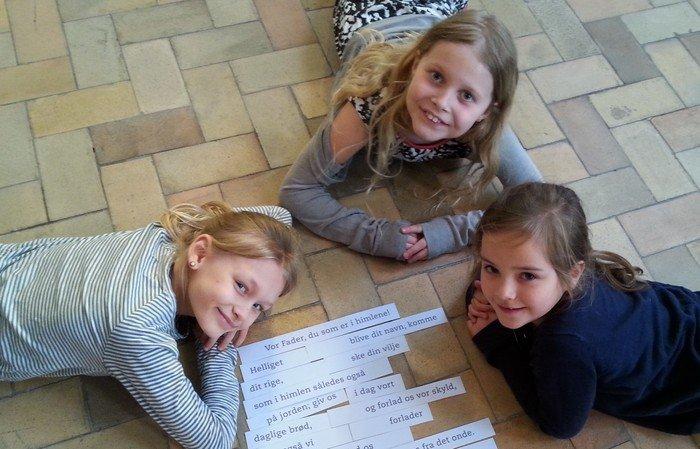 3 smilende piger ligger på kirkegulvet