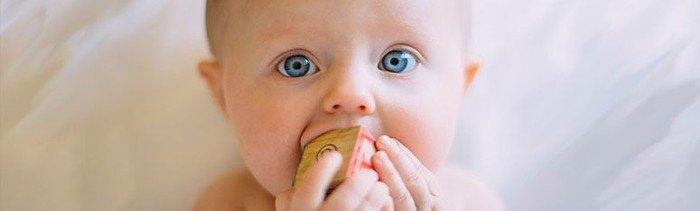 Billede af baby som bider i en legeklods