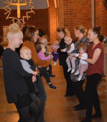På billedet ses to rækker af forældre med deres babyer