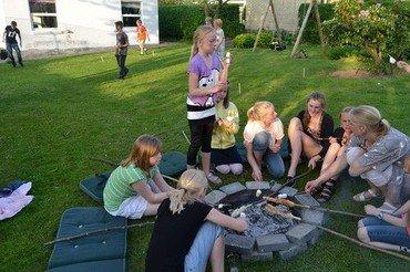 Billede af børn, der sidder omkring et bål