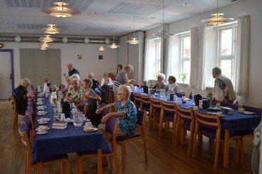 Billede af ffredagsÅben deltagere ved bordene i sognehuset