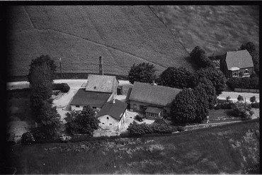 """Vindinge Brødfabrik, fotograferet fra luften 1949. Bagermester Oluf Christiansens flotte bil står foran stuehuset. Yderst til højre ses aftægtshuset fra 1927, hvor hans mor Anna stadig boede. I skellet sydøst for stuehuset anes """"Dampmøllehulen""""."""