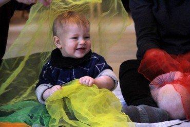 Smilende baby, der sidder og lege på gulvet med gult ciffontørklæde