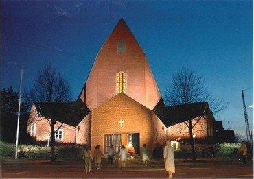 Foto af oplyst kirke i mørke, hvor mennesker er på vej ind af den åbne dør