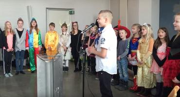 Børn der er klædt ud til fastelavn og som er samlet i kirkerummet