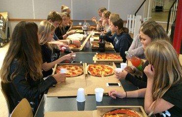 Konfirmander spiser pizza i KonfirmandCaféen siddende på begge sider af et langt bord