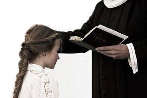 En præst er ved at konfirmere en pige