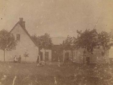 Gården set fra øst. Det er antagelig Johanne og Hans ved stuehusets gavl. Til højre laden med grovbryggers, tærskeværk og hestestald i den modsatte ende. I vestlængen var der ko- og svinestald.
