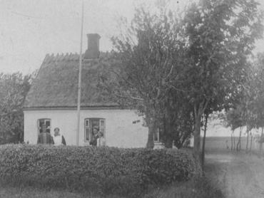 """Johanne og Hans ved indkørslen til gården 1928-30. Bag dem Magda og i haven Gerda og sandsynligvis Hans Rasmussen. Indgangen til Stuehuset var fra gården, i nordøst-hjørnet var soveværelset, mod sydøst lå stadsstuen. I midten var hverdagsstuen, og bag det lille vindue i vestenden kammeret, hvor lille Hans overnattede sammen med sin mor. Mod nordvest nær staldlængen lå """"storkøkkenet""""."""