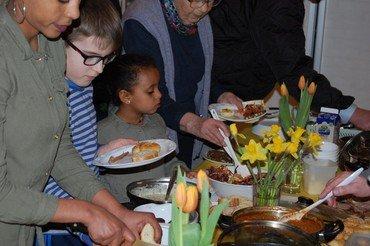 Close-up billede af to børn og to voksne, som tager mad fra buffeten.