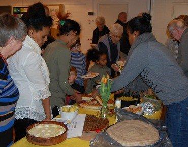 Mennesker af forskellige etniciteter tager mad fra fælles buffet.