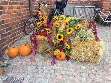 Græskar, solsikker og halmballer foran kirken
