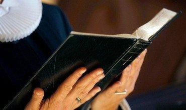 Hænder der holder en opslået bibel