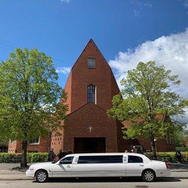 Foto af Hyltebjerg Kirke med en limousine parkeret foran
