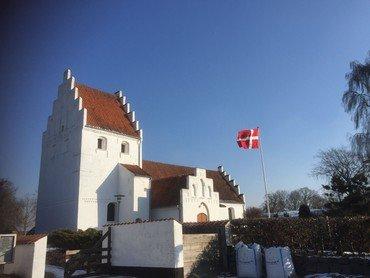 Allesø kirke, blå himmel og flag som står flot vandret i vinden
