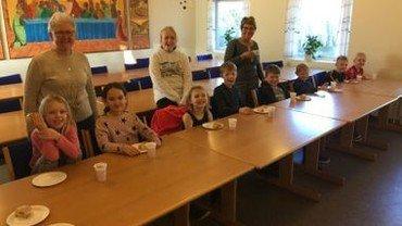 Seks børn siddende på stole ved bord i det store lokale i Sognegården, og Maja som står op samt voksne Karin og Birgit