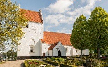 Næsbyhovedbroby kirke med grønne træer til højre og venstre for. let skyet