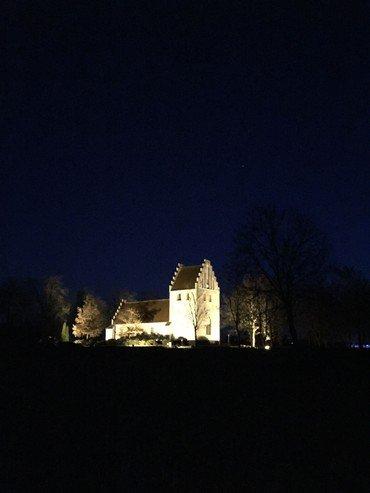 Natbillede af Næsbyhovedbroby Kirke. kirken er stærkt belyst med en dyb blå himmel som kontrast