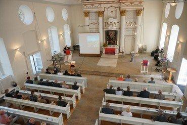 Das Kirchenschiff von der Empore aus gesehen mit den Besucher*innen des Gottesdienstes
